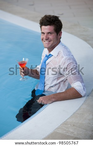 Young man having a drink in the pool, his clothes on