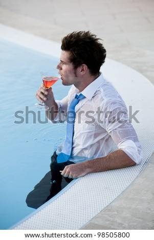 Young man having a drink in the pool, his clothes on - stock photo