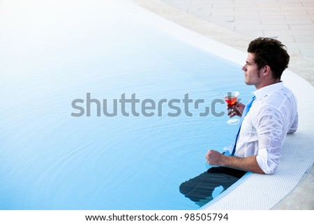 Young man having a drink in the pool, his clothes on, lots of copy-space - stock photo