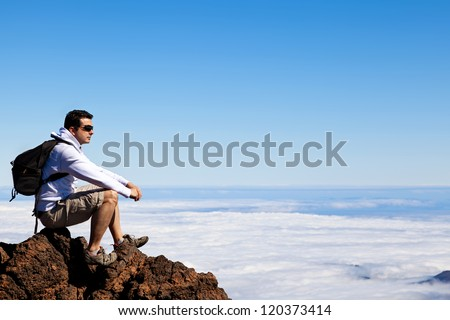 Young Man Having a Rest in a High Peak Over Clouds in Teide Mountain - stock photo