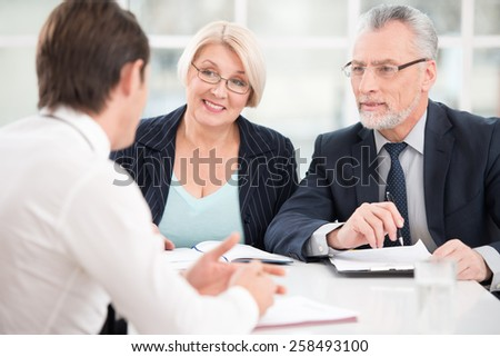 Young man having an interview or business meeting with employers. Office interior with big window
