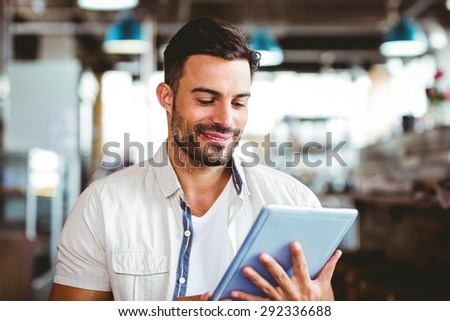 Young man having cup of coffee using tablet at the cafe - stock photo