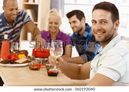 Young man having dinner party with friends, smiling, drinking wine, looking at camera. - stock photo