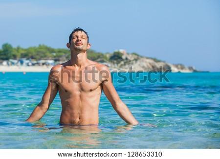 Young man having fun in oceans water - stock photo