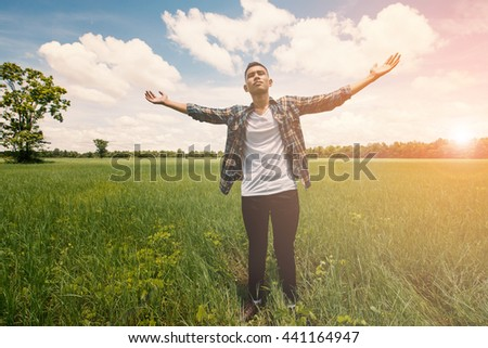 Young man having happy time in nature with copy space on meadow background
