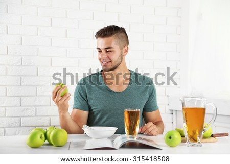 Young man having light breakfast  - stock photo