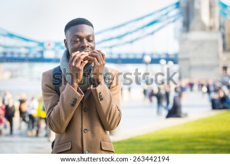 Young man having lunch break in London next to Tower Bridge. He is seated on a concrete low wall and is eating a sandwich. - stock photo