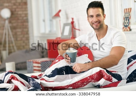 Young man having morning tea in bed, smiling happy, looking at camera. - stock photo