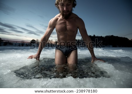 Young man having recreational swim in the ice hole - stock photo