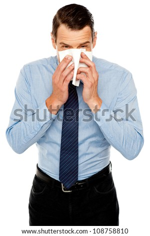 Young man having severe cold. Sneezing and cleaning nose with tissue paper - stock photo
