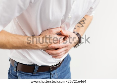 Young man having stomach pain - stock photo