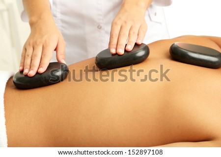 Young man having stone massage in spa salon