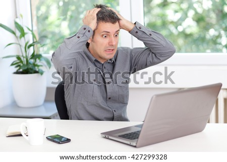 Young man having trouble with laptop - stock photo