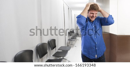 young man headache in office or waiting room - stock photo