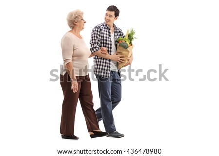 Young man helping a senior lady with her groceries isolated on white background - stock photo