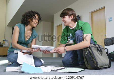 Young man helps friend to pick up papers in corridor