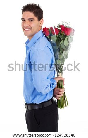 young man hiding bunch of red roses behind his back - stock photo