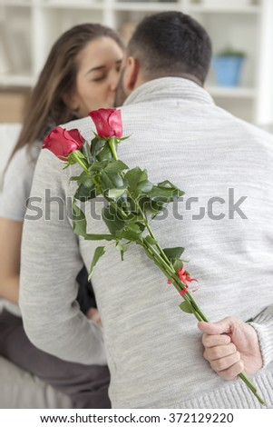 Young man hiding flowers behind his back, kneeling and kissing with girlfriend - stock photo