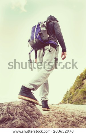 Young man hiker hiking on the beach - stock photo