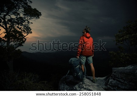 Young man hiker in red jacket standing on the rock and enjoying sunset over valley - stock photo