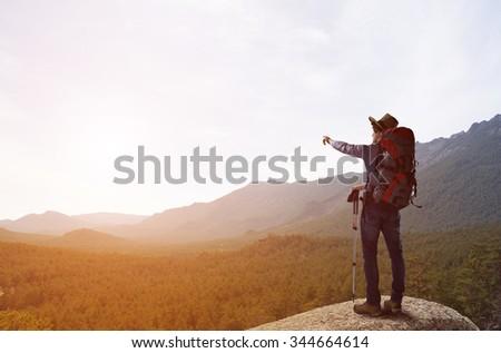 Young man hiker walking in beautiful mountain nature landscape  - stock photo