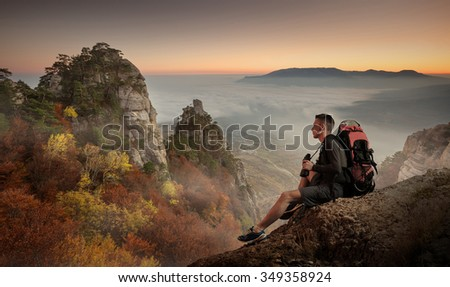 Young man hiker with backpack and binoculars sitting on a cliff and enjoying a Mountain view. - stock photo