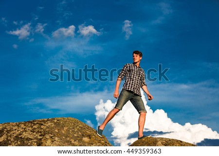 Young man hiking in front of blue sky
