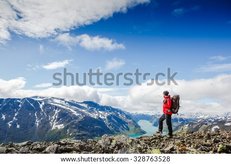 Young man Hiking in in the mountains. Besseggen Ridge. Yotunheimen national park. Norway - stock photo