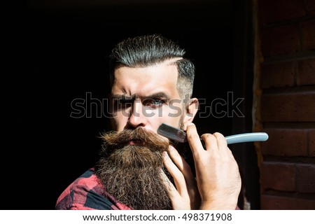 Young man hipster with handsome bearded face holding cut throat razor near long fashion beard and moustache on black background studio