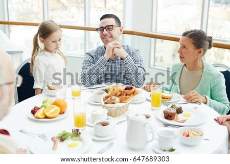 Young man, his daughter and mature woman sitting by served table