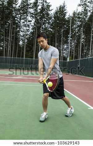 Young man hitting two handed backhand on outdoor tennis court with trees in background