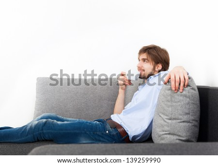 young man hold cup of coffee think relaxing sitting on couch, sofa home indoors, happy guy smile day dreaming with tea mug in hands looking up in thought to empty wall with copy space