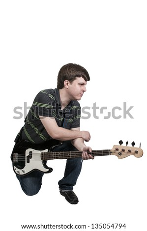 Young man holding a bass guitar musical instrument - stock photo