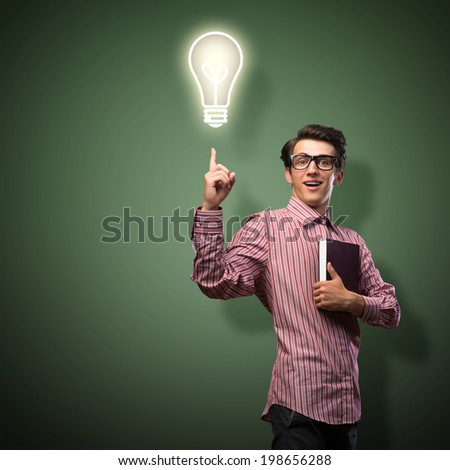 young man holding a book in front of him, raised his hand, the idea - stock photo