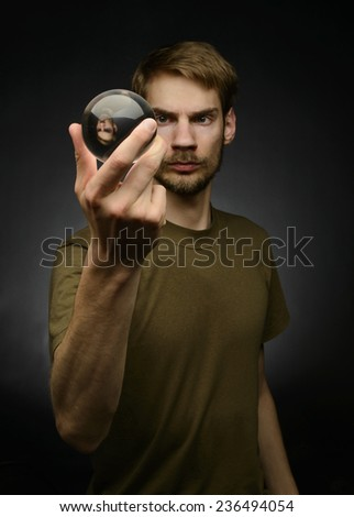 Young man holding a clear transparent crystal glass ball in their hand - stock photo