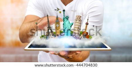 Young man holding a cloud full of famous monuments of the world over his digital tablet - stock photo
