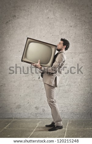 Young man holding a CRT television - stock photo