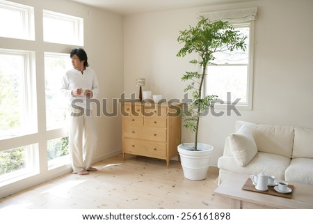 Young man holding a cup of tea and looking out of a window - stock photo