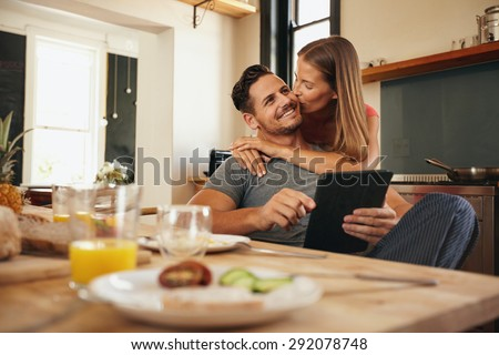 Young man holding a digital tablet while his girlfriend hugs him from behind, giving him a good morning kiss. Young love couple in morning at the kitchen. - stock photo