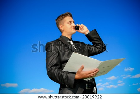 Young man holding a folder while talking on the phone. - stock photo