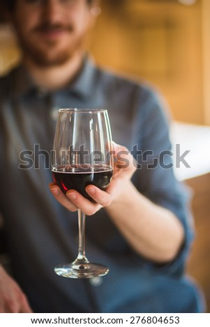 Young man holding a glass with red wine and smiling at camera