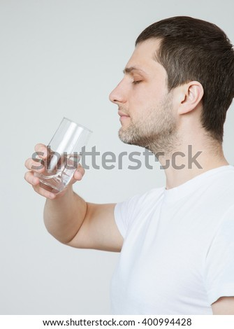 Young man holding a glass with water, closeup shot