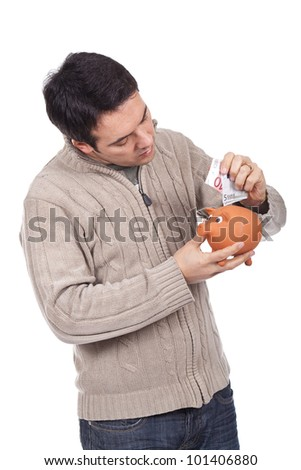 young man holding a piggy bank and putting euro bills inside it