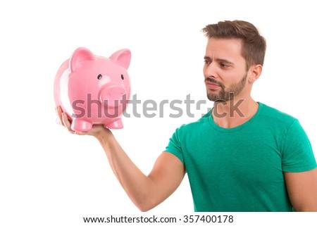 Young man holding a piggy-bank - money concept - stock photo