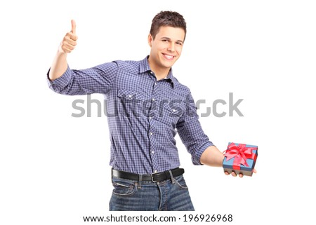 Young man holding a present and giving thumb up isolated on white background - stock photo