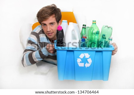 Young man holding a recycling bin - stock photo