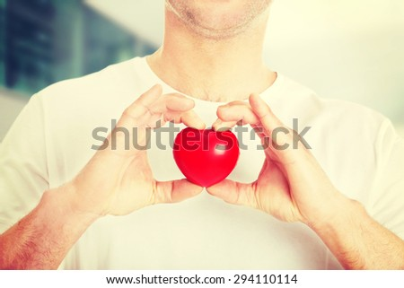 Young man holding a red heart toy