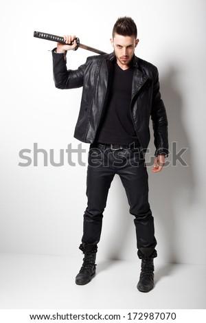 Young man holding a samurai sword. Glamour photo. - stock photo