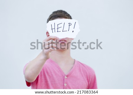 Young man holding a sign calling for help - stock photo
