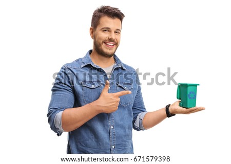 Young man holding a small recycling bin and pointing isolated on white background